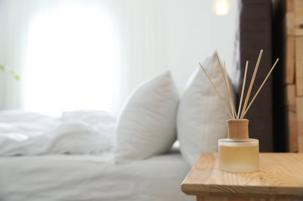 reed diffuser on nightstand of clean white bed