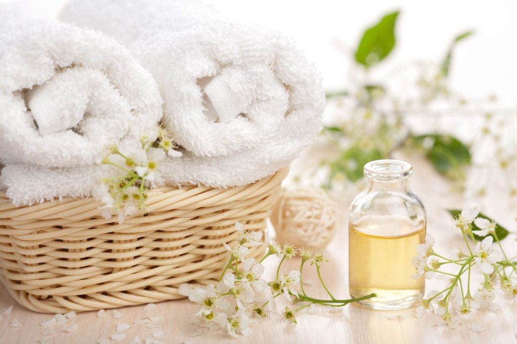 aromatherapy white folded towel in basket next to essential oil bottle with yellow oil and flowers